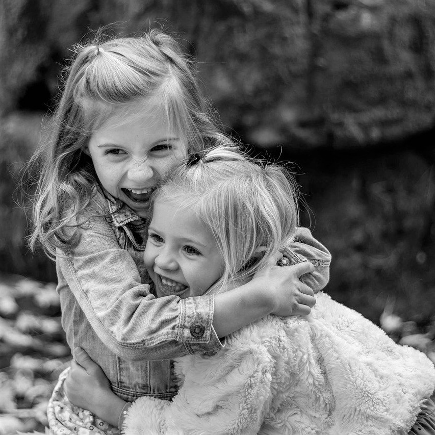 zwei Mödchen die sicih freudig umarmen