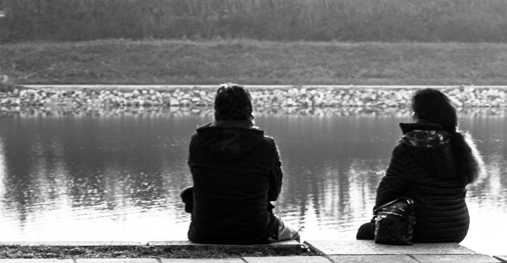 Zwei Menschen sitzen am Ufer der alten Donau in Wien.