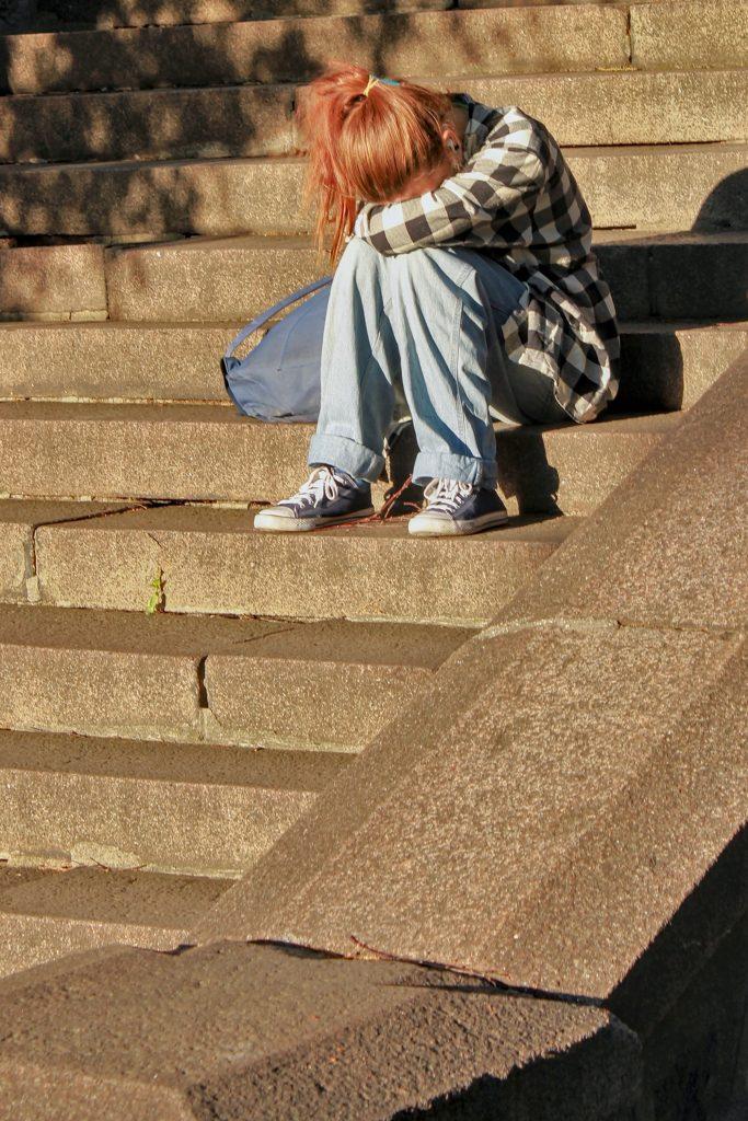 Traurige und einsame Schülerin auf Treppe. Folgen einer möglichen Traumatisierung durch die Schule.